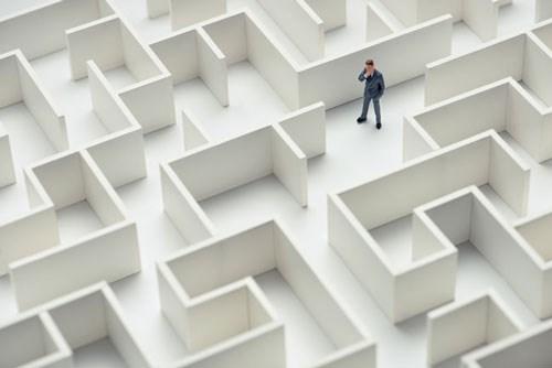 An image of a businessman navigating through a maze. Top view