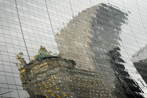 A distorted reflection coming from two opposite buildings on a glass facade of another building