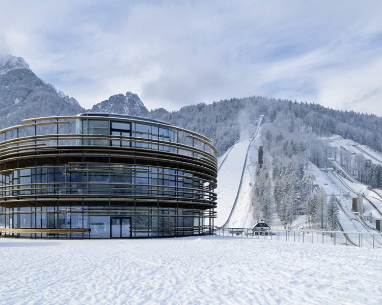 central building of Planica Nordic Center overlooking the ski jumping hills
