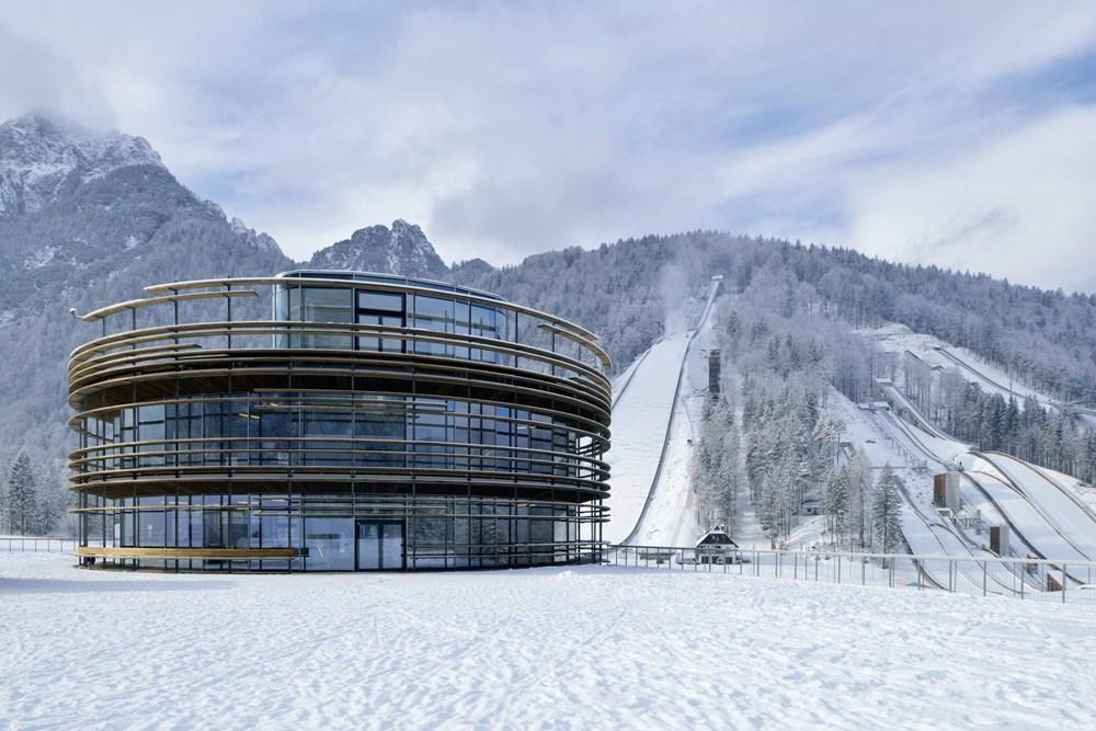 clădirea centrală a Planica Nordic Center cu vedere de la dealurile de sărituri cu schiurile