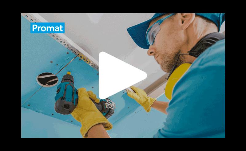 Snimka zaslona videozapisa na kojem radnik u plavoj majici, sa zaštitnim naočalama i žutim rukavicama, postavlja plavo obojanu ploču na strop.