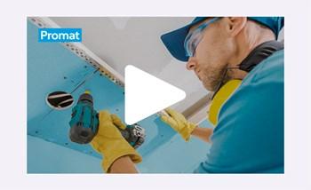 Slika zaslonskega zajema videa, v katerem delavec v modri majici, z zaščitnimi očali in rumenimi rokavicami, na strop vgrajuje modro obarvano požarno ploščo.