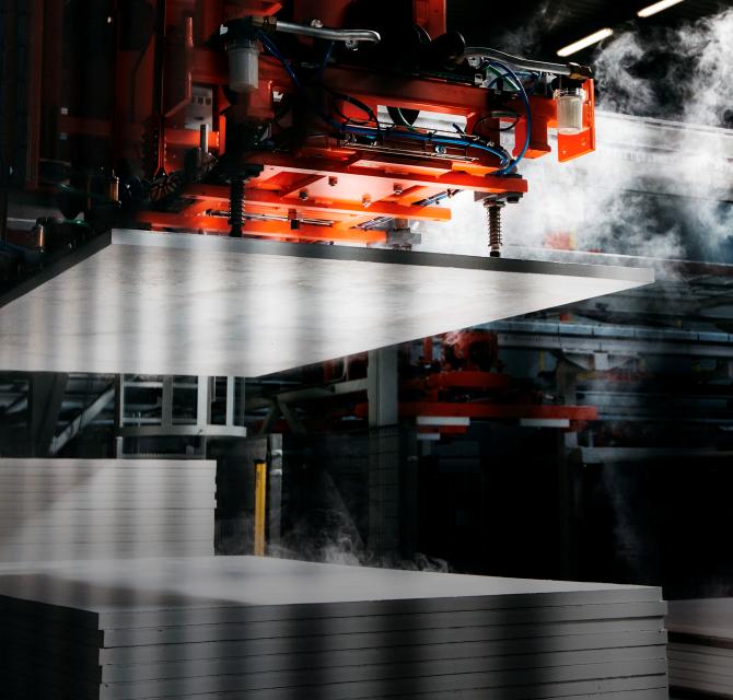 Na slici su palete protupožarnih ploča tijekom procesa proizvodnje u industrijskom pogonu, jedan stroj podiže ploču iznad ostalih.