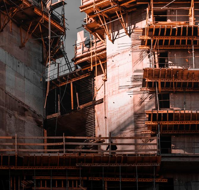 Slika jedne strane zida građevine tijekom postupka gradnje s drvenim skelama i vidljivom čeličnom unutarnjom konstrukcijom zgrade.